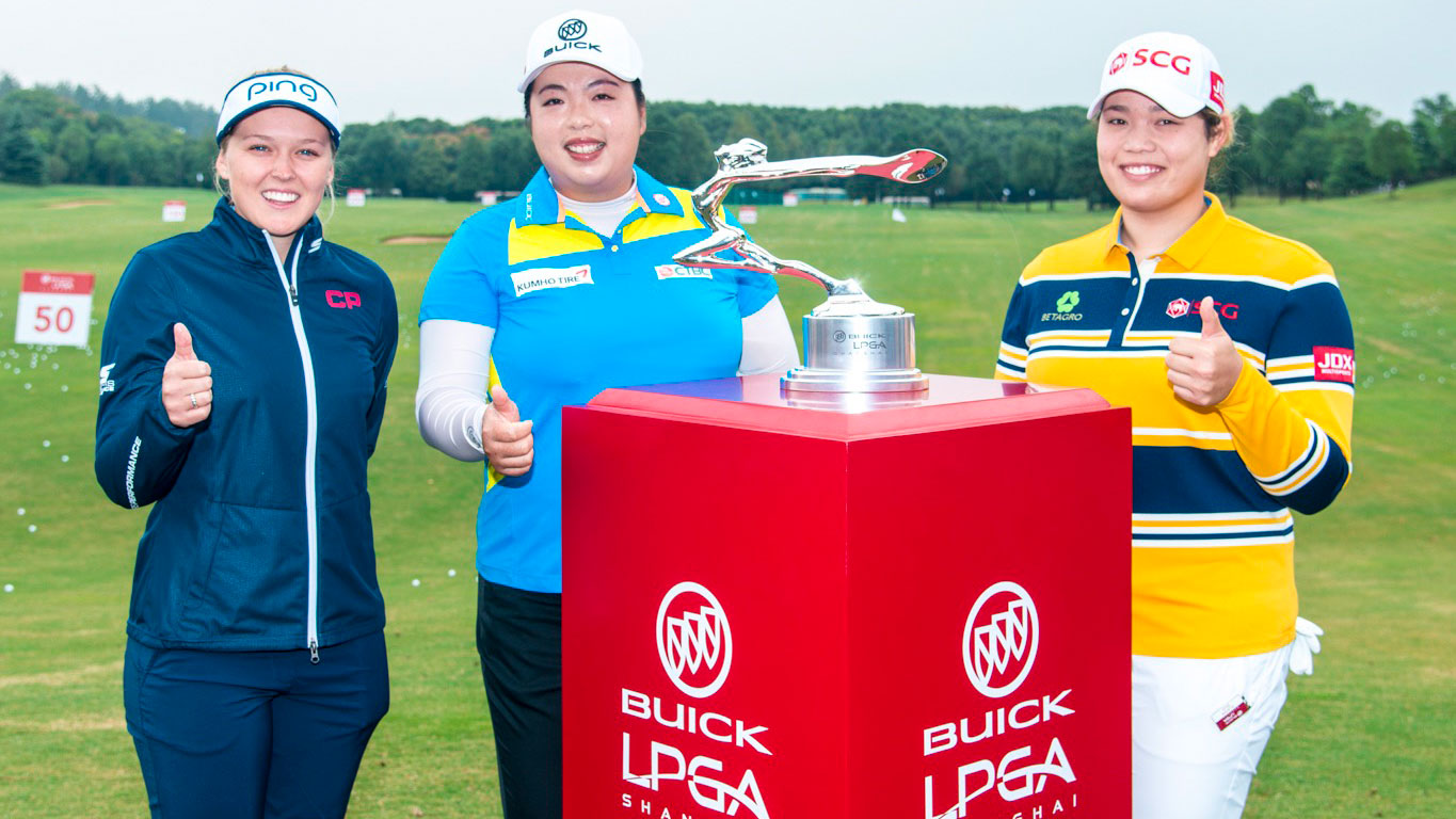 Brooke Henderson (left) and Ariya Jutanugarn (right) join Shanshan Feng in front of the Buick LPGA Shanghai trophy