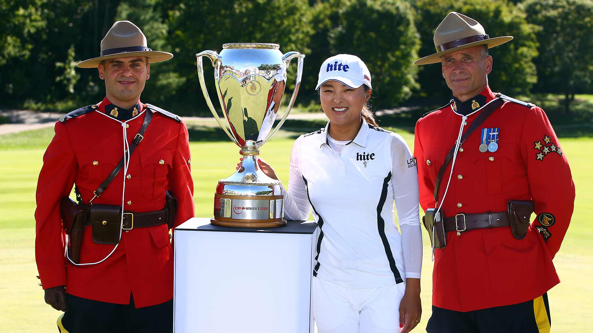 Jin Young Ko of Korea poses with the CP Women's Open Championship Trophy and Canadian Mounties following the final round at Magna Golf Club on August 25, 2019 in Aurora, Canada