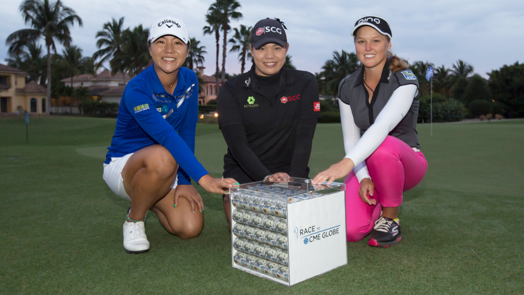 Lydia Ko (Left), Ariya Jutanugarn (Center) and Brooke Henderson pose with the $1 Million Race to CME Globe prize money