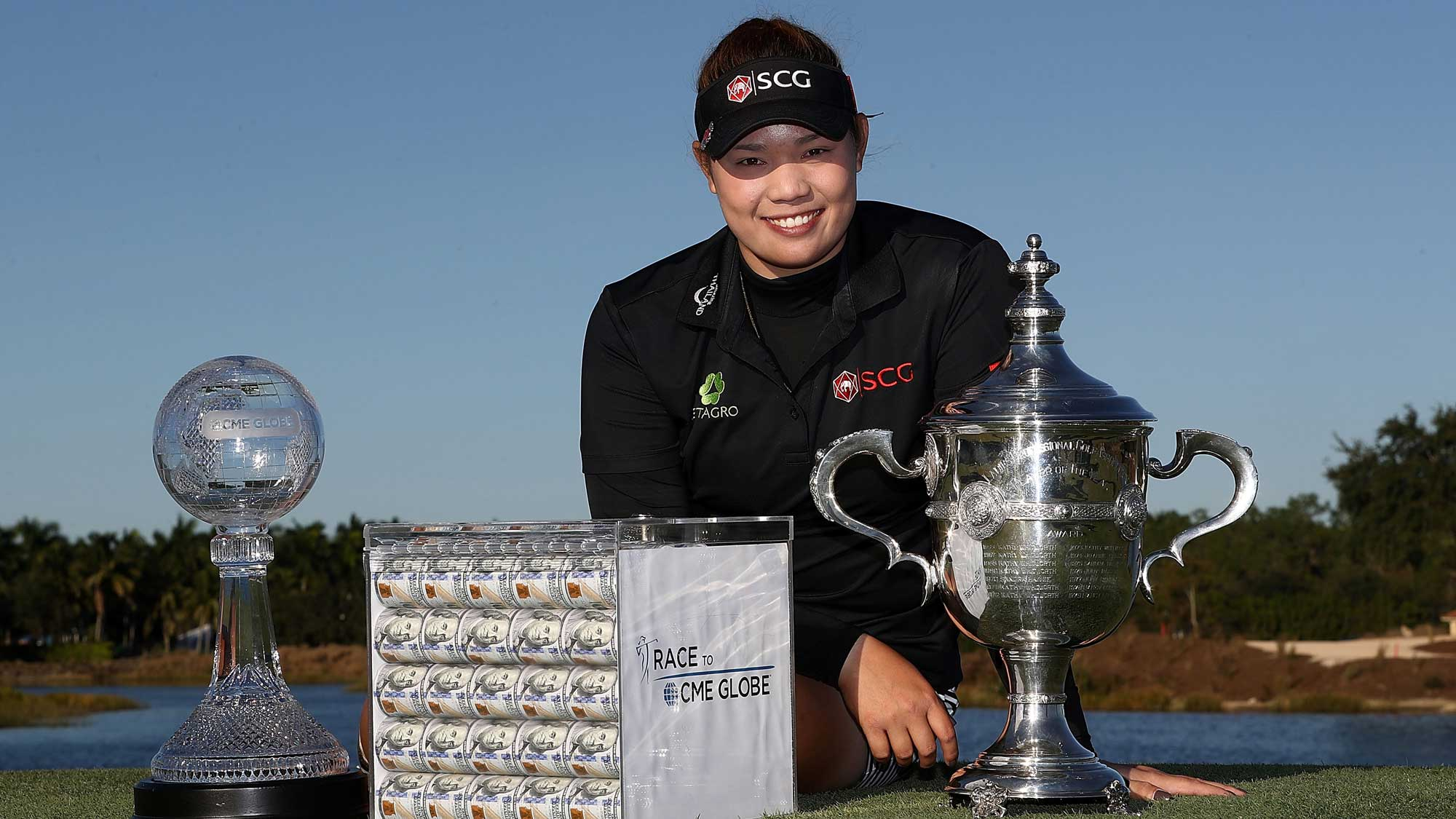 Ariya Jutanugarn of Thailand poses with the Rolex Player of the Year trophy, the CME Race for the Globe trophy and a box of one million dollars in cash during the final round of the CME Group Tour Championship at Tiburon Golf Club