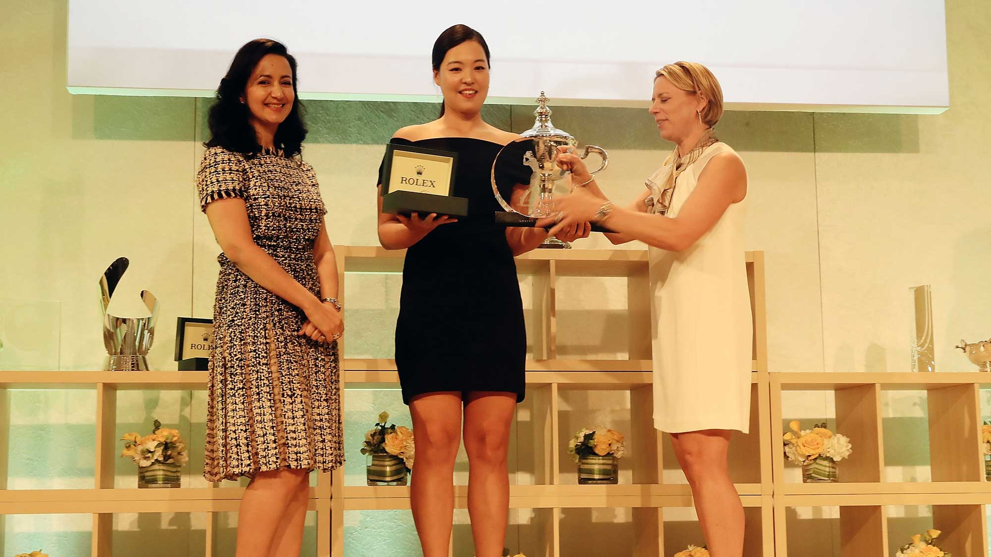 Mounia Mechbal (Left) and Annika Sorenstam (right) present In Gee Chun of Korea with the Rookie of the Year award at the Rolex LPGA Awards