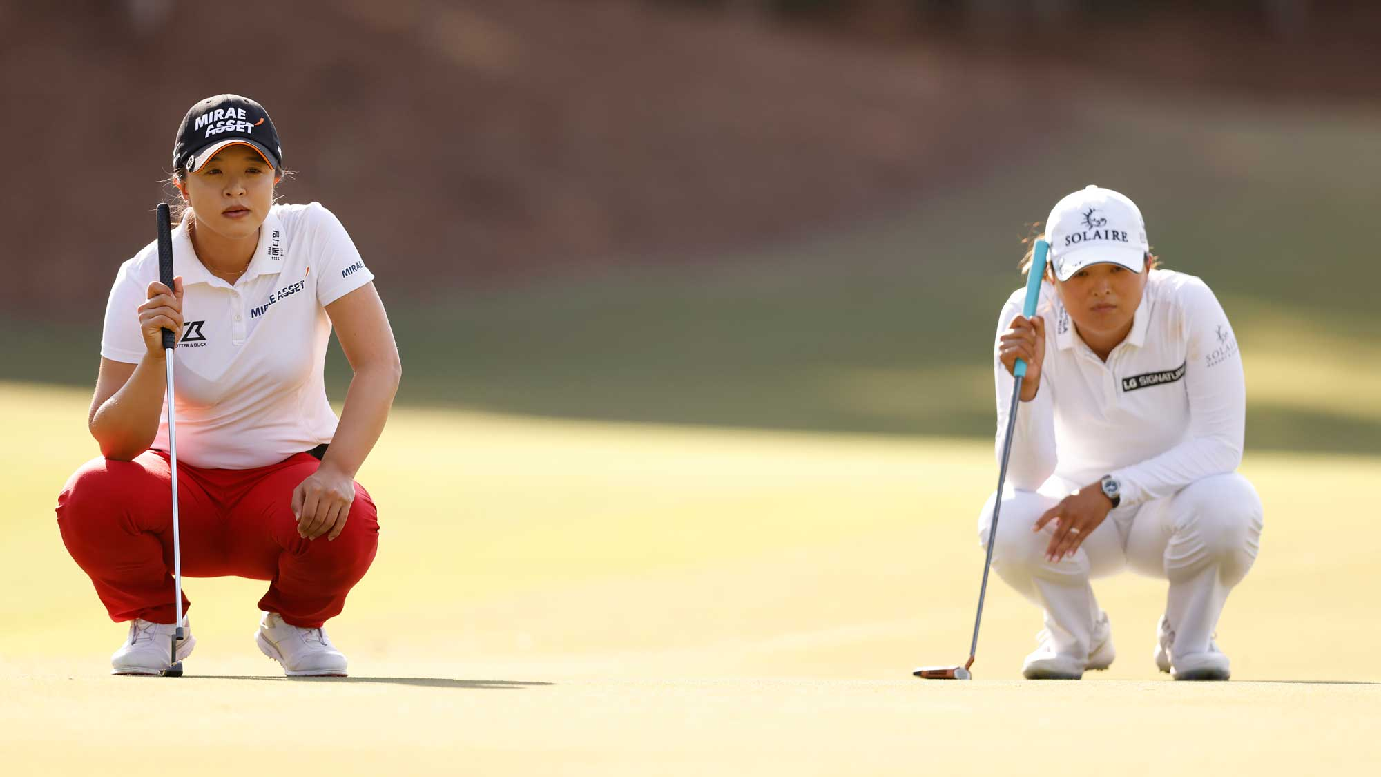 Jin Young Ko of Korea and Sei-Young Kim of Korea look over their putt on the third green during the final round of the CME Group Tour Championship
