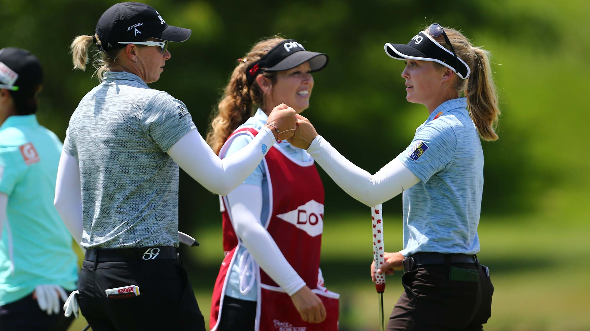 Alena Sharp of Canada celebrates with Brooke Henderson of Canada on the ninth hole after their first round of the Dow Great Lakes Bay Invitational