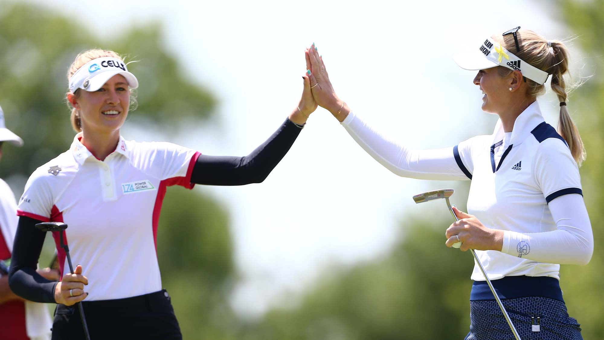 Nelly Korda (L) high five Jessica Korda on the eighth hole during the first round of the Dow Great Lakes Bay Invitational