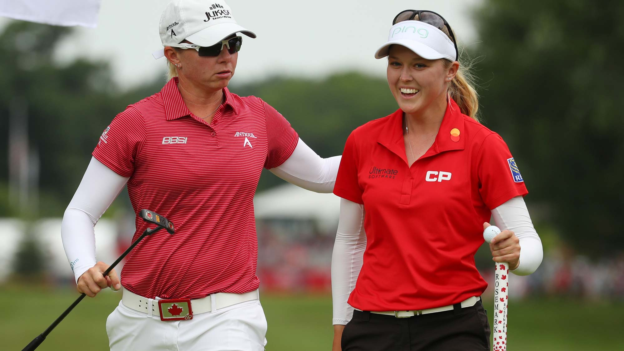 Teammates Brooke Henderson (R) and Alena Sharp walk off the first green during round two of the Dow Great Lakes Bay Invitational