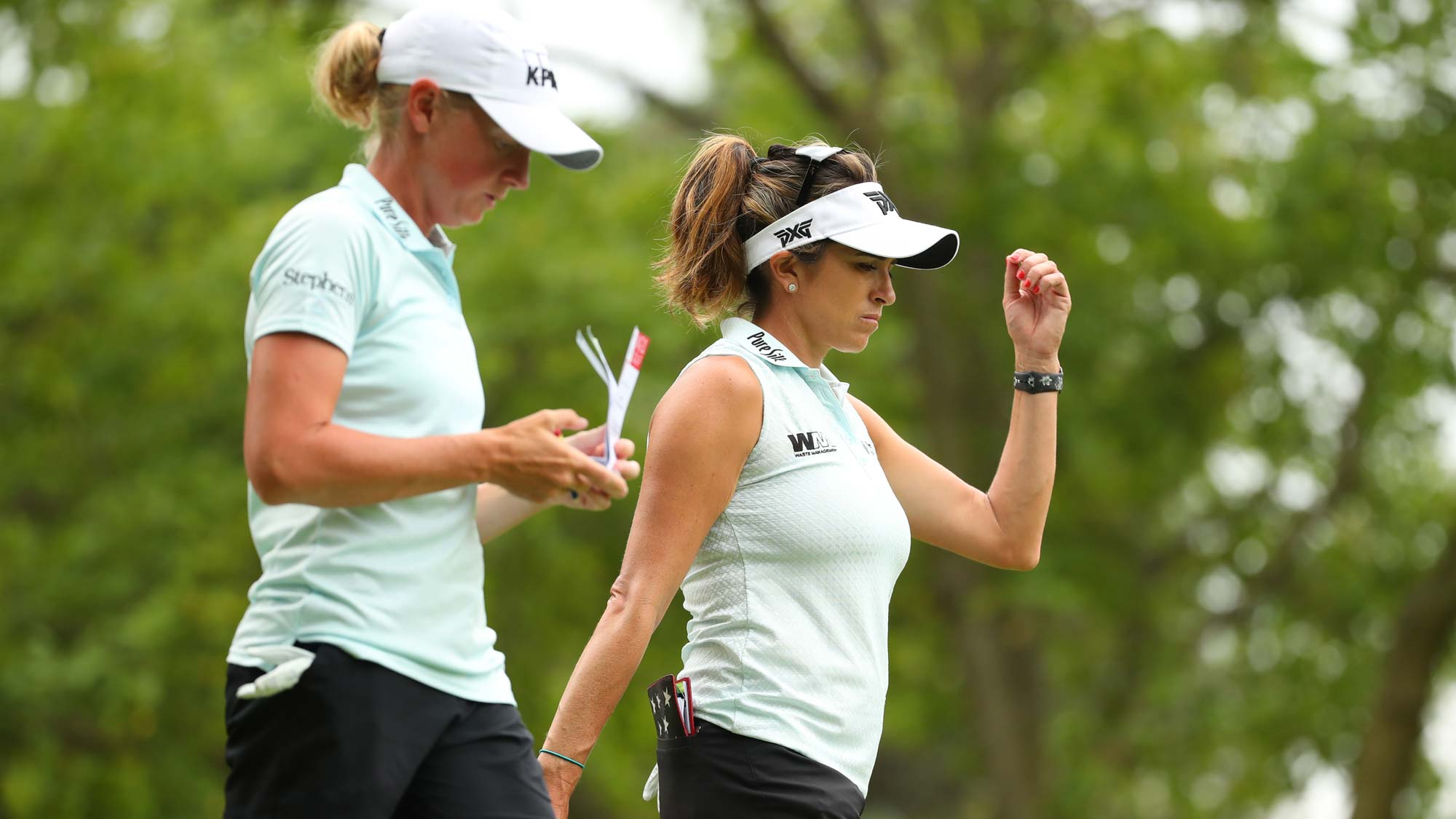 Teammates Stacy Lewis (L) and Gerina Piller walk off the second tee during round two of the Dow Great Lakes Bay Invitational