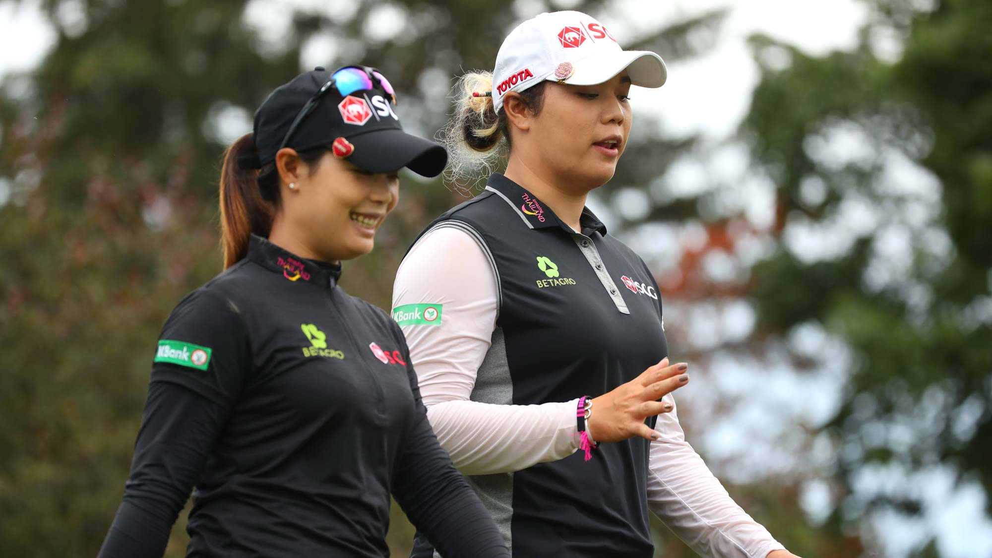 Teammates Moriya Jutanugarn (L) and Ariya Jutanugarn walk off the sixth tee during the final round of the Dow Great Lakes Bay Invitational