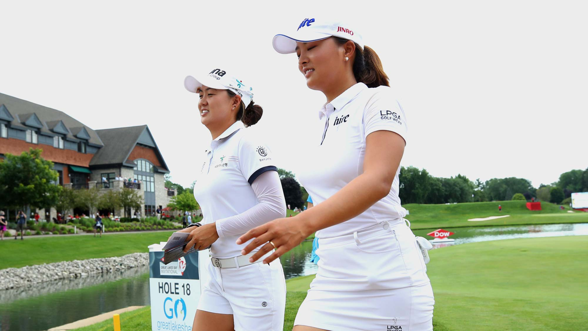 Teammates Minjee Lee of Australia (L) and Jin Young Ko of South Korea walk off the 18th green after their final round of the Dow Great Lakes Bay Invitational
