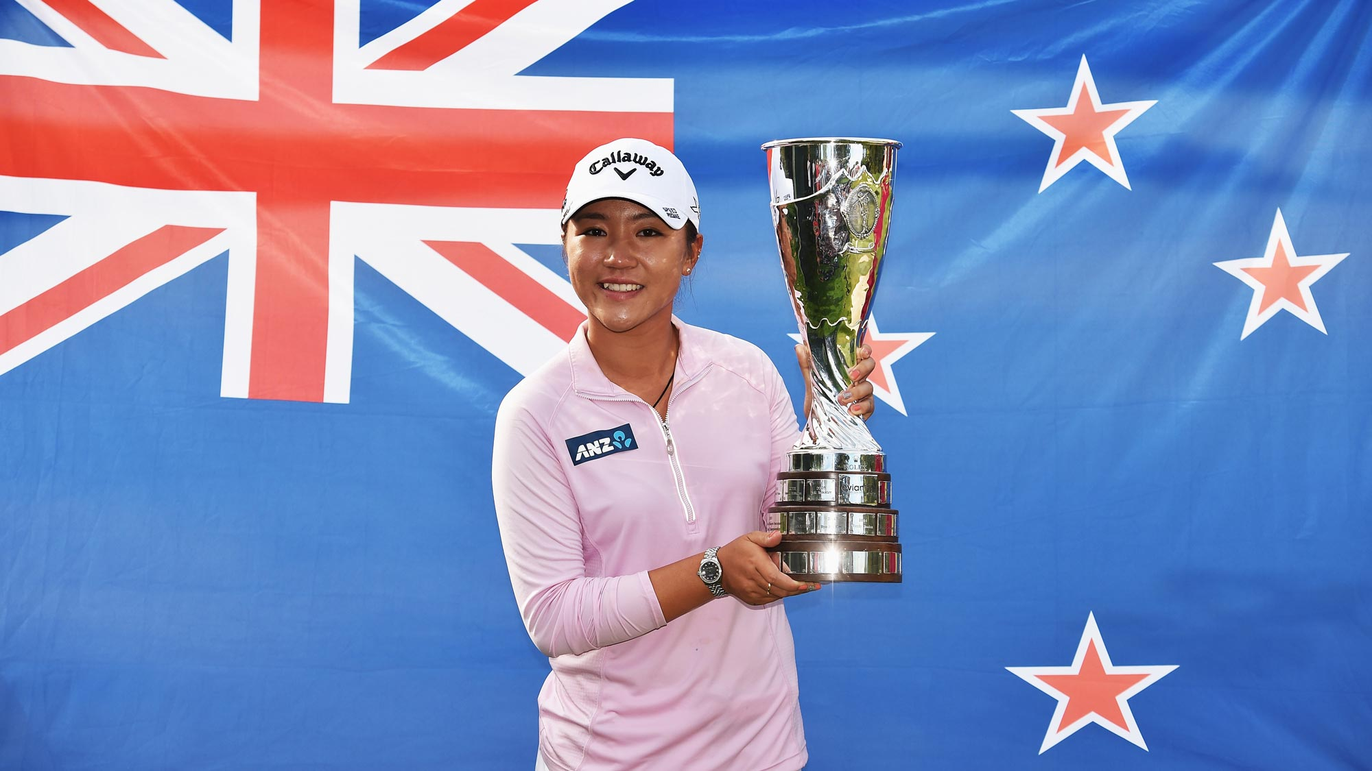 Lydia Ko posing with the Evian Championship Trophy in front of the official flag of New Zealand