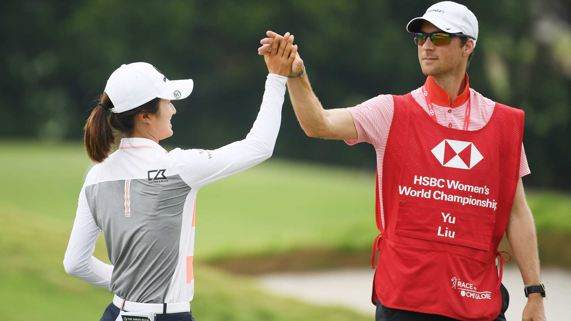 Yu Liu of China celebrates with her caddie on the 18th hole during the first round of the HSBC Women's World Championship at Sentosa Golf Club on February 28, 2019 in Singapore.
