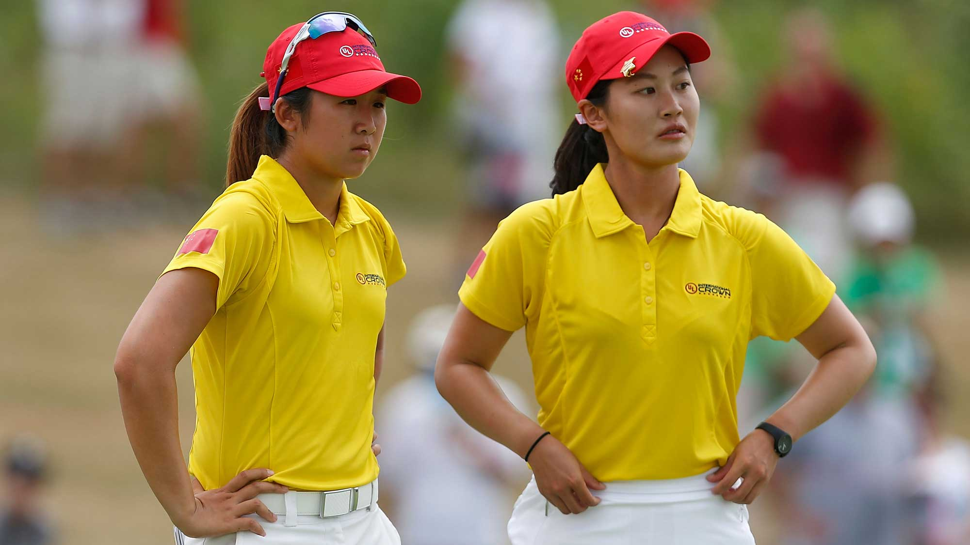 (L) Jing Yan and (R) Xi Yu Lin of China wait on the third green during the four-ball session of the 2016 UL International Crown