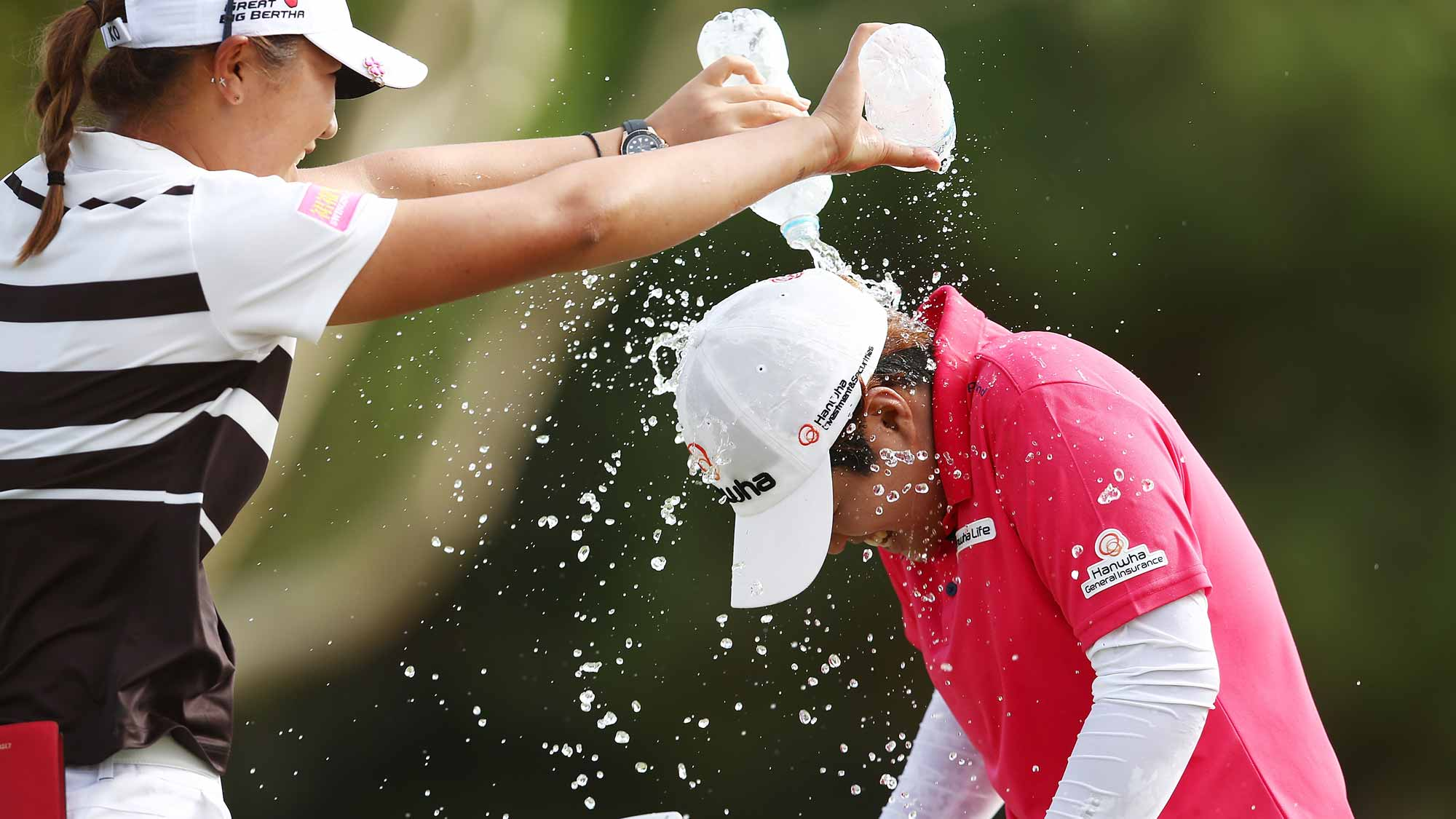 Haru Nomura of Japan runs away from Lydia Ko of New Zealand as Ko tries to dump water on her head in celebration after Nomura won the Women's Australian Open
