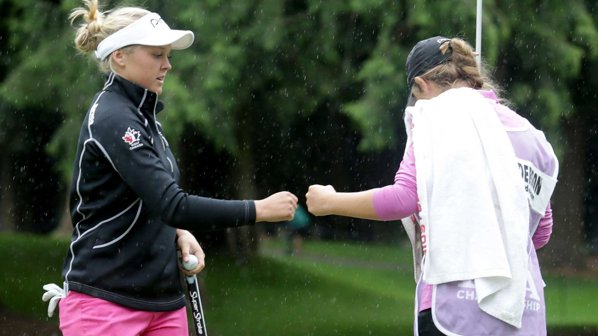 Brooke Henderson of Canada is congratulated by her sister/caddie Brittany after making a birdie putt on the ninth hole during the first round of the KPMG Women's PGA Championship