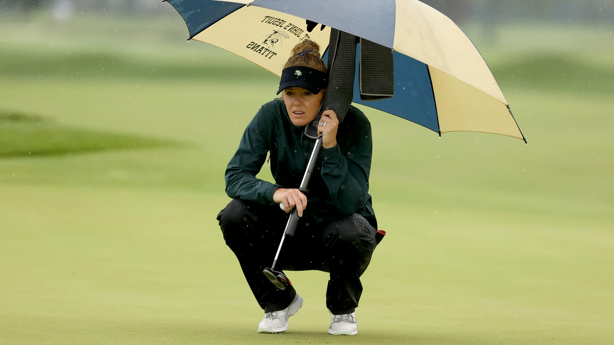 Amy Olson lines up a putt on the second green under an umbrella to avoid the rain during the second round of the LPGA Drive On Championship