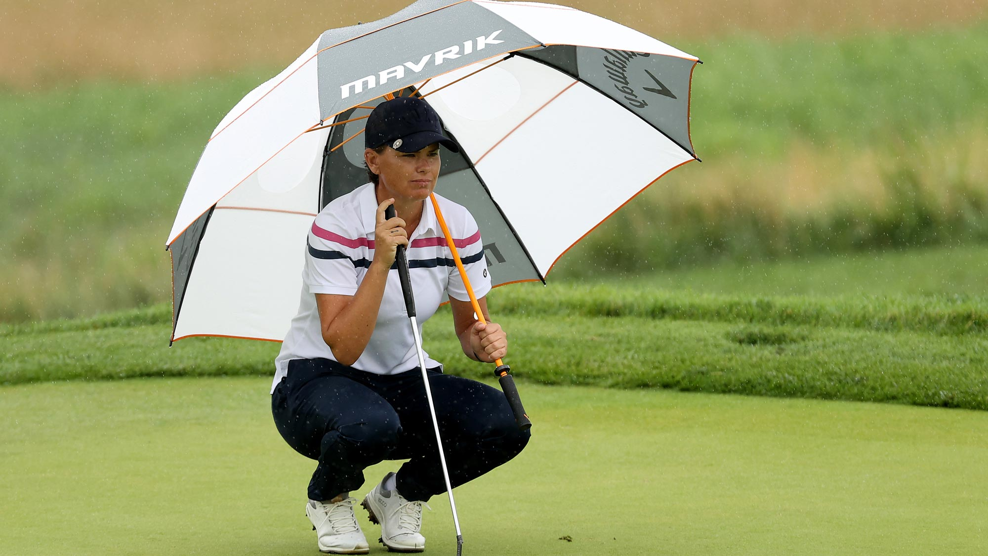 Lee-Anne Pace of South Africa lines up a putt on the fourth green under an umbrella to avoid the rain during the second round of the LPGA Drive On Championship