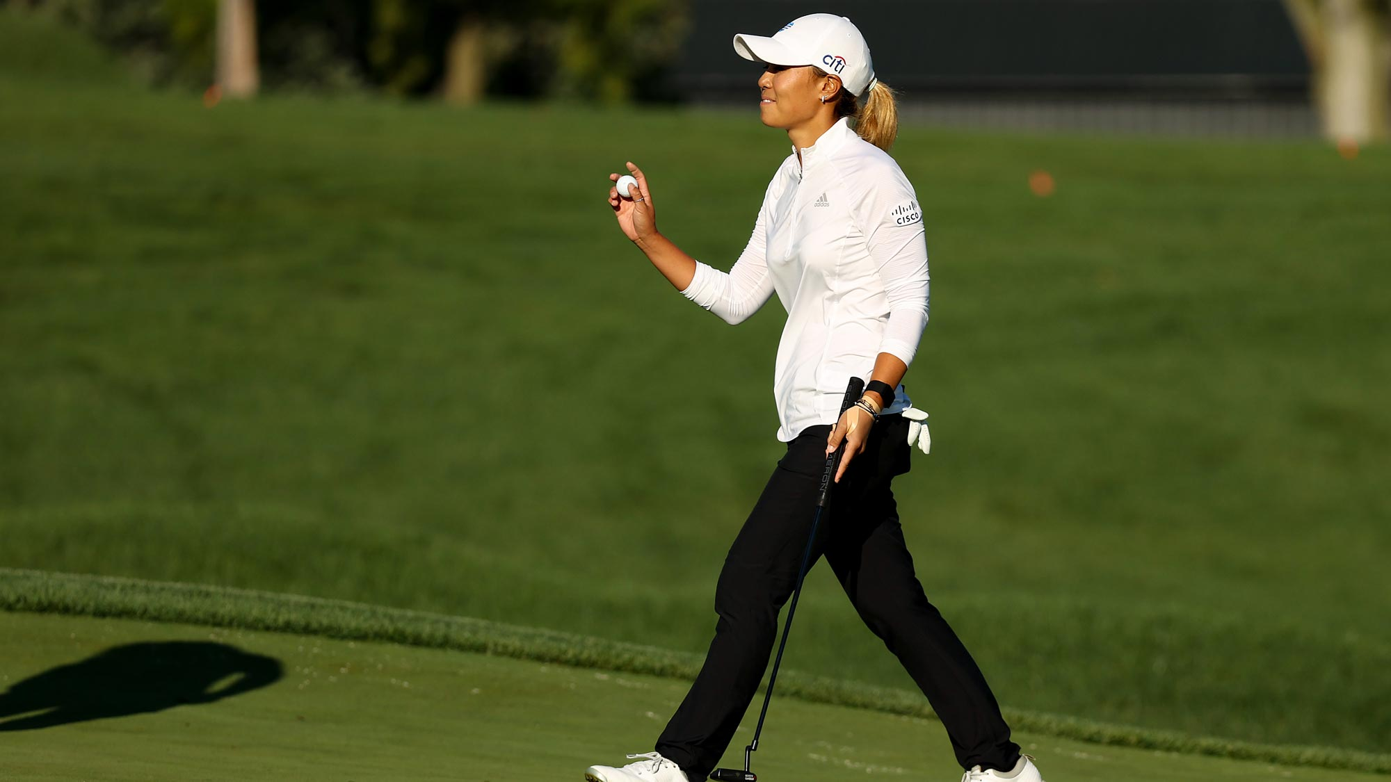 Danielle Kang retrieves her ball after putting for par on the 18th hole to win the LPGA Drive On Championship