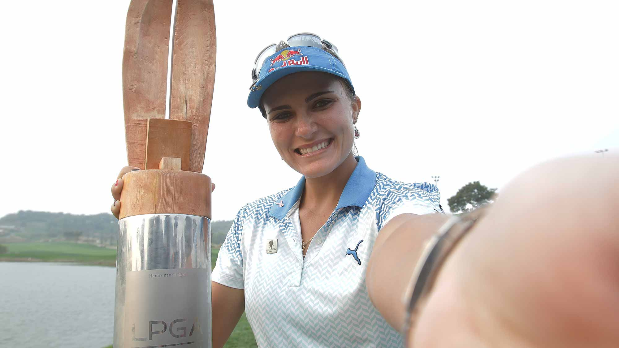 Lexi Thompson of United States imitates a 'selfie' as she poses with the trophy during a ceremony following the LPGA KEB Hana Bank
