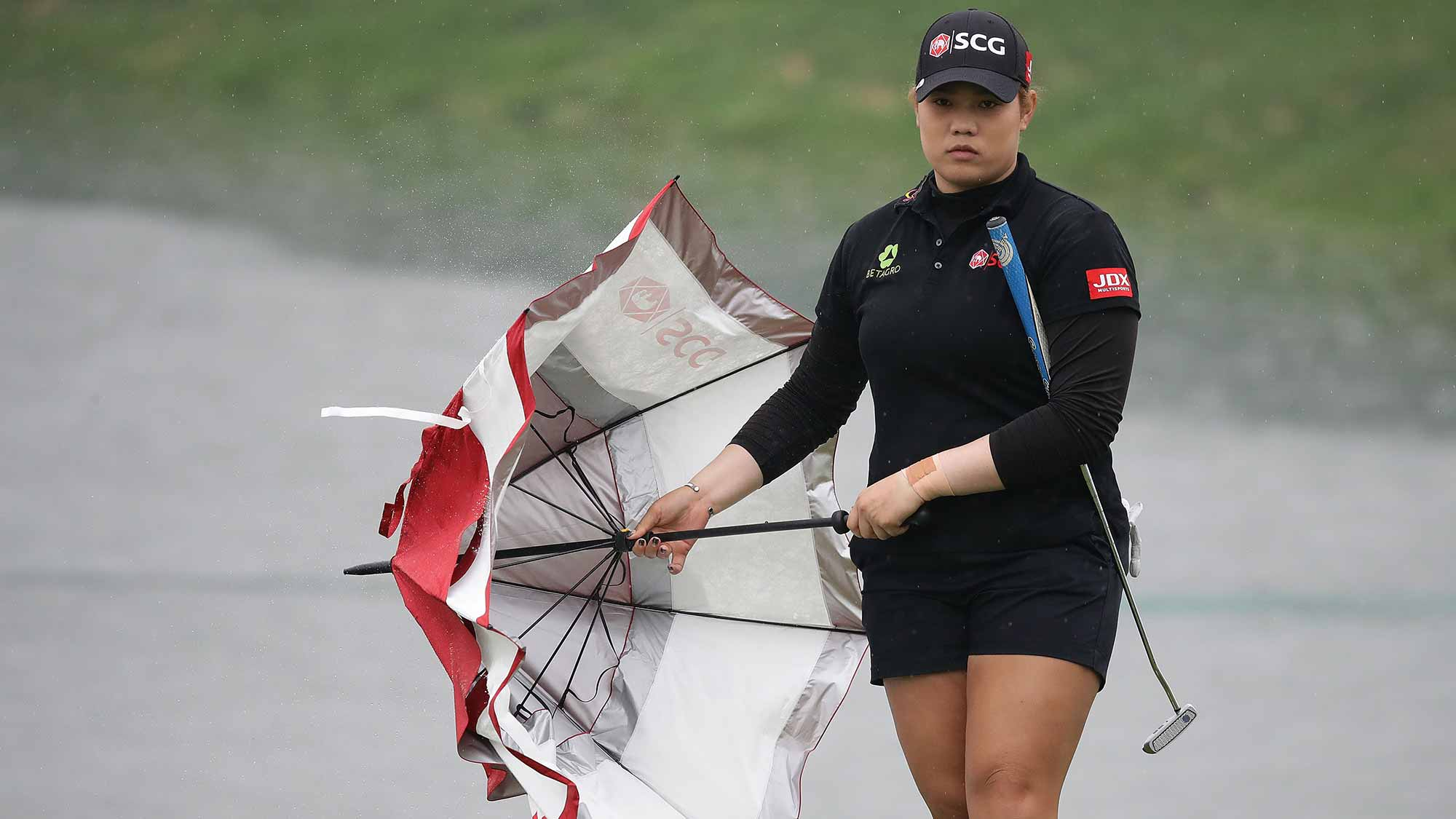 Ariya Jutanugarn of Thailand wear black clothing to mourn the death of King Bhumibol on the 18th green during the final round of the LPGA KEB-Hana Bank Championship at the Sky 72 Golf Club Ocean Course
