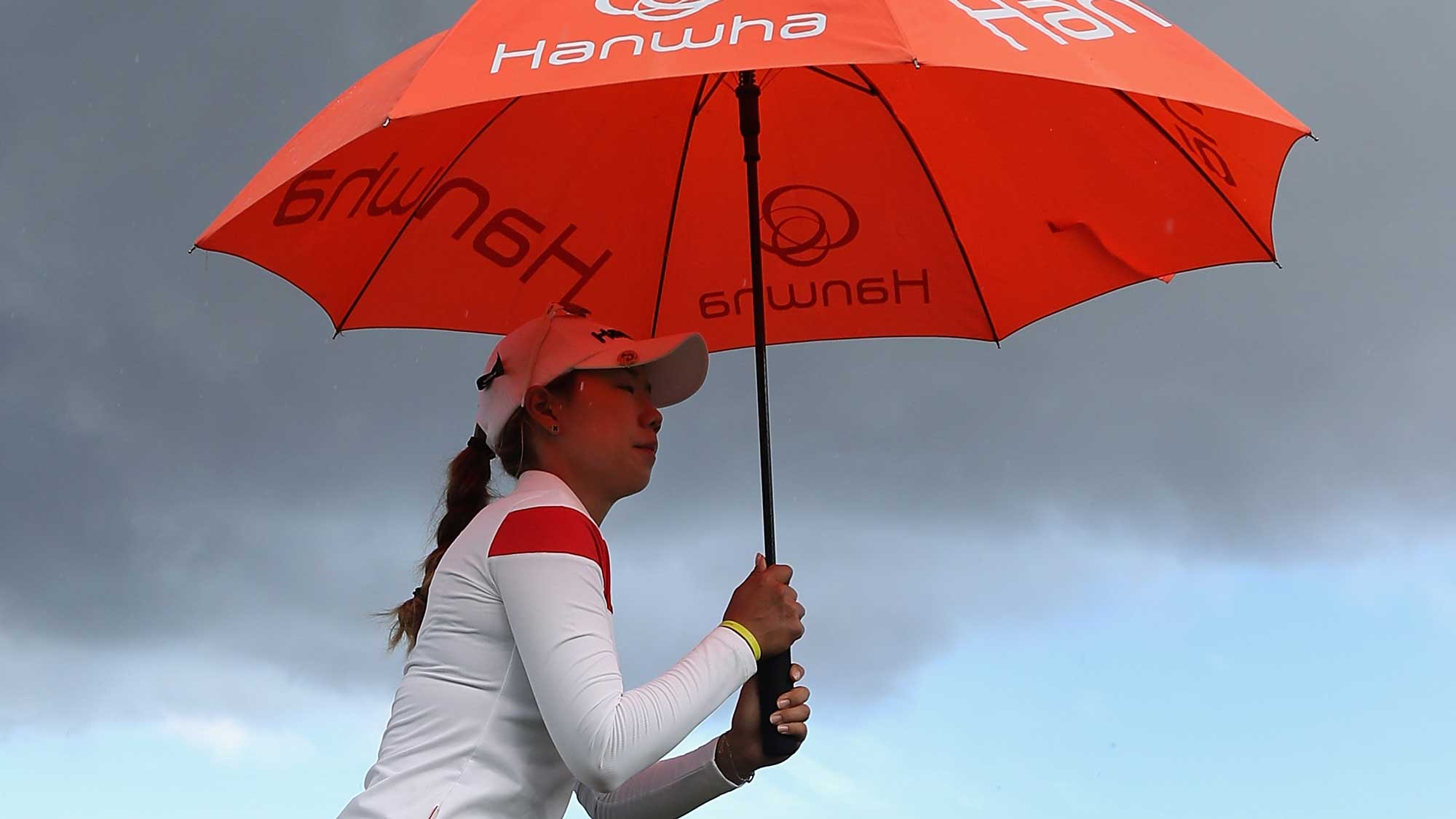 Jenny Shin of the Republic of Korea holds up an umbrella in the rain on the 10th hole during the first round of the LPGA LOTTE Championship Presented By Hershey