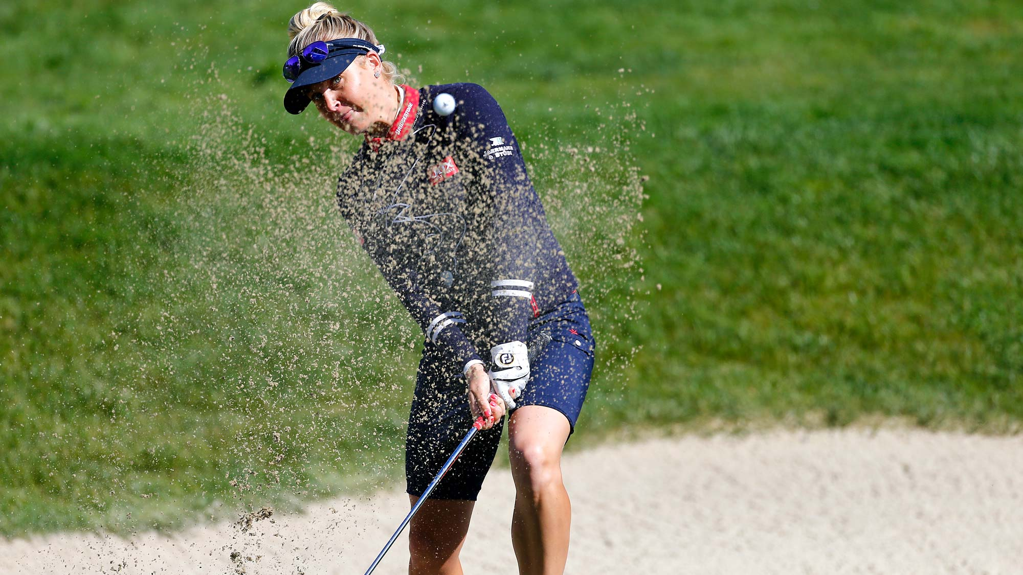 Charley Hull of England hits out of the bunker on the 18th hole during the first round of the LPGA Mediheal Championship