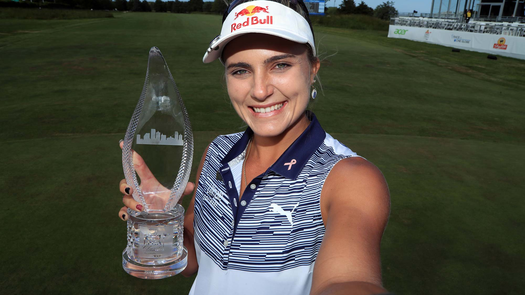 "Lexi Thompson imitates a ""selfie"" as she holds the championship trophy after winning the ShopRite LPGA Classic presented by Acer"