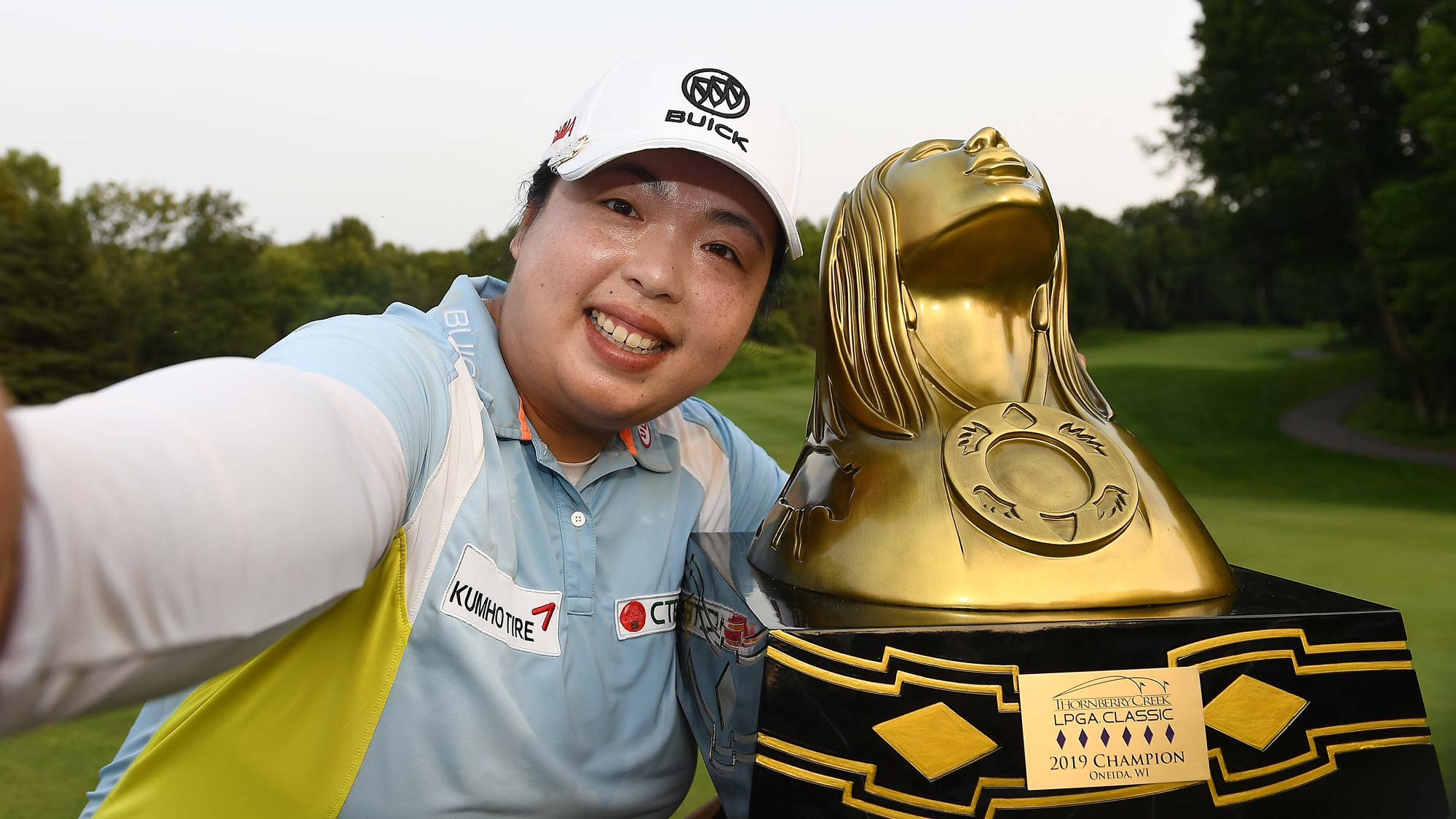 "Shanshan Feng of China imitates a ""selfie"" as she poses with the trophy after winning the Thornberry Creek LPGA Classic"