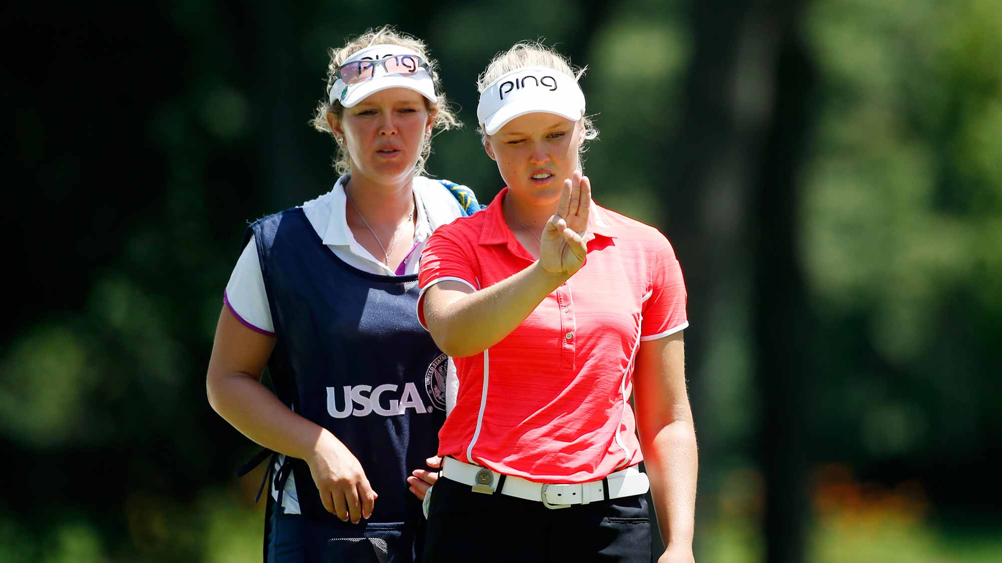 Brooke Henderson of Canada lines up a putt with her sisiter/caddie Brittany on the 16th green during the second round of the U.S. Women's Open at Lancaster Country Club