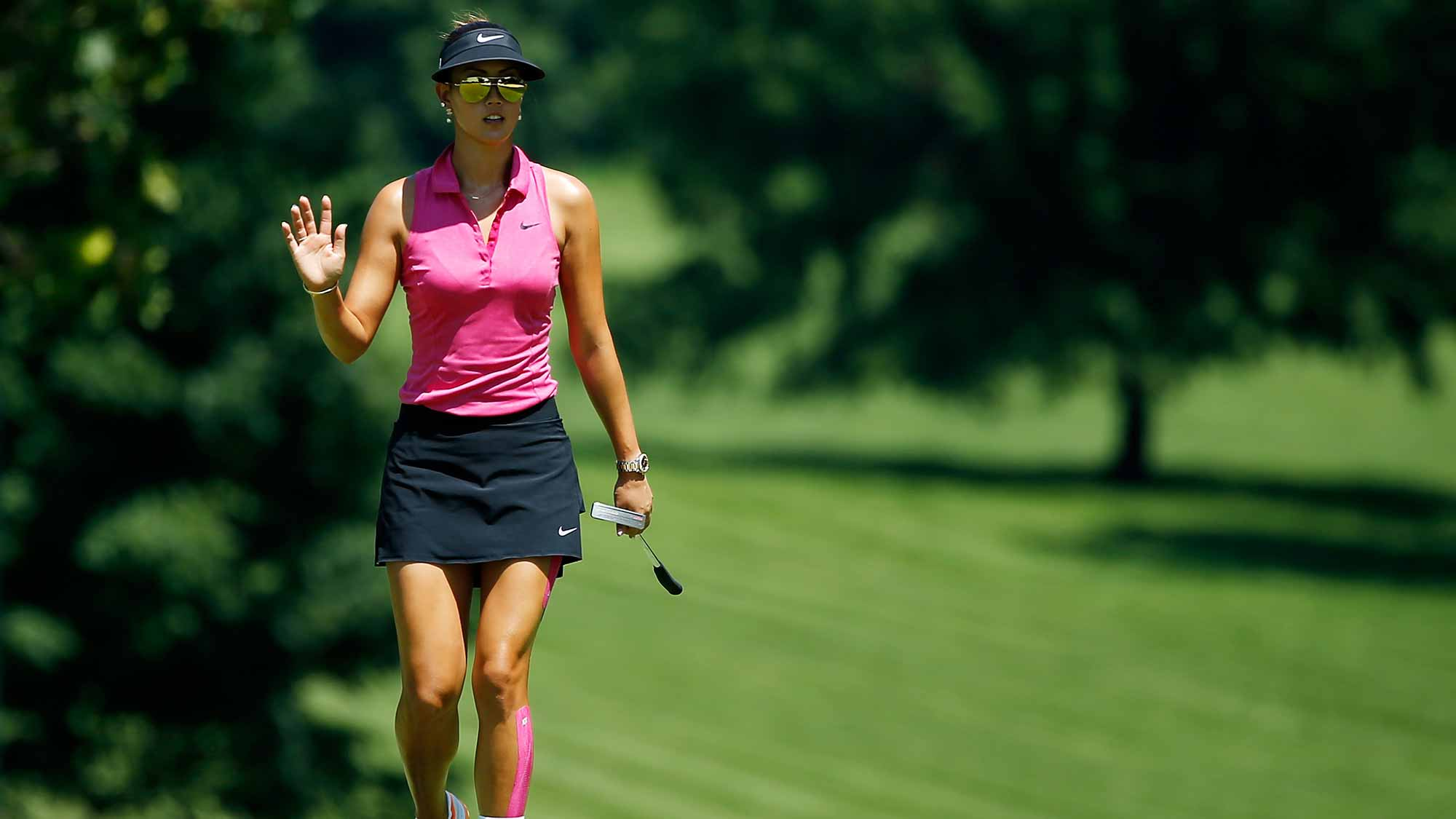 Michelle Wie of the United Staes waves as she walks to the eighth green during the third round of the U.S. Women's Open at Lancaster Country Club