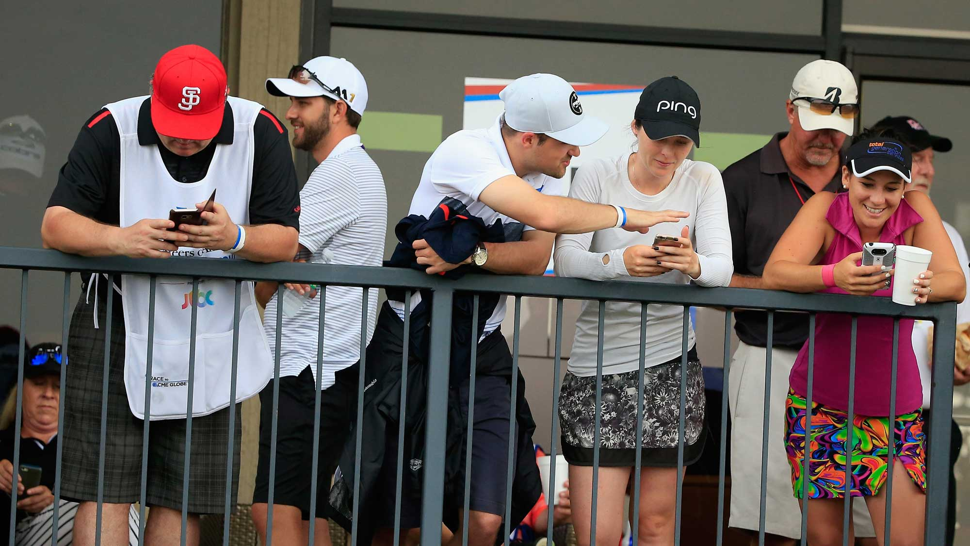 Players and caddies wait near the clubhouse after play was suspended by dangerous weather during the second round of the Volunteers of America Texas Shootout