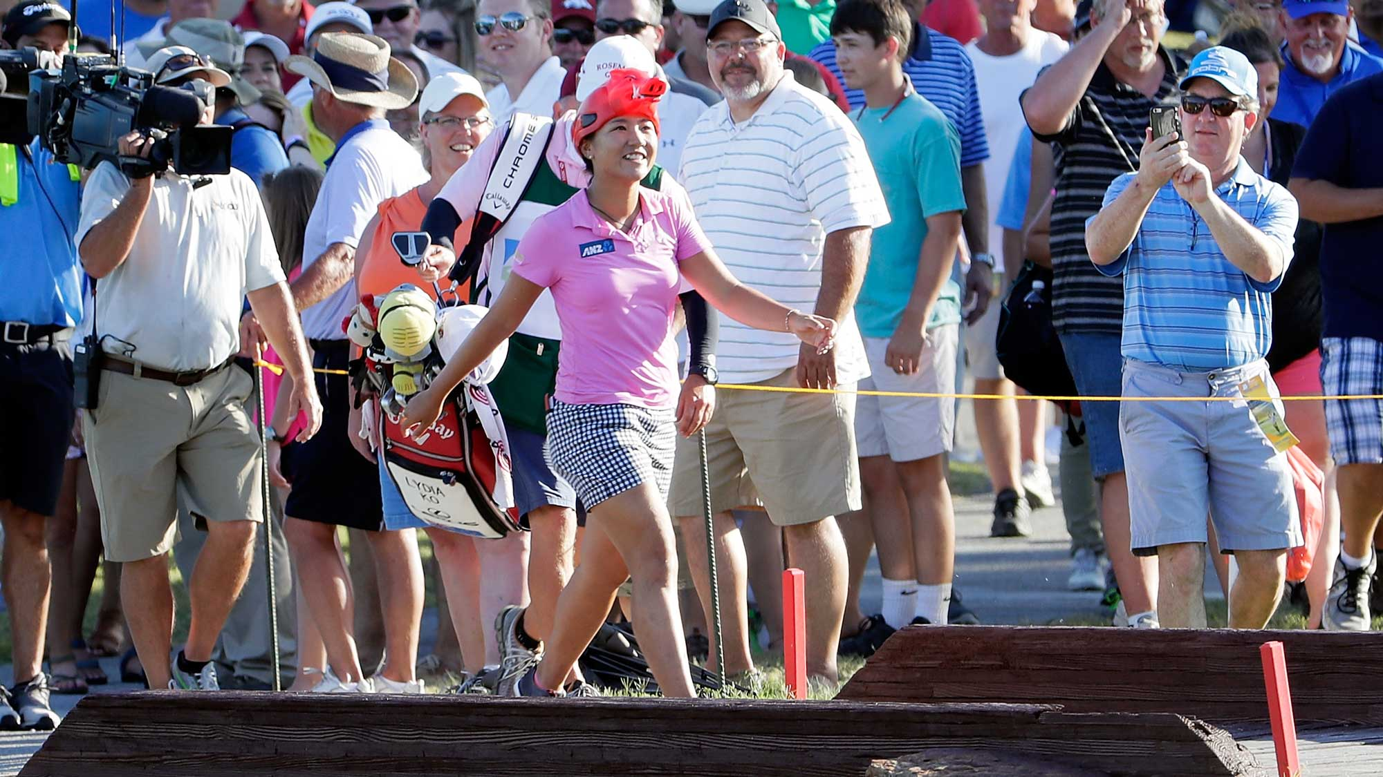 Lydia Ko of New Zealand walks toward the green on the 17th hole wearing an Arkansas Razorbacks hat on her way toward winning the Walmart NW Arkansas Championship